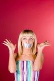La blonde dans le studio sur un fond rouge photo stock