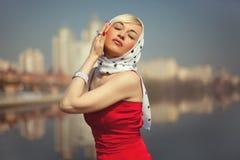 La blonde dans une robe rouge a fermé ses yeux Image stock