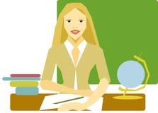 La blonde de femme de professeur s'assied à un bureau à l'arrière-plan d'un tableau noir Image stock
