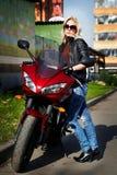 La blonde de fille au sujet d'une moto rouge Images libres de droits