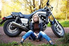 La blonde de fille s'assied au sujet d'une grande moto Photographie stock