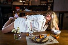 La blonde drôle dans le peignoir se trouve sur la table avec la nourriture contre la cuisine moderne images stock