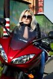 La blonde en glaces se reposant sur la moto rouge Images stock