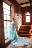 La blonde enceinte de jeune mariée dispose à devenir une mère et une épouse Longue robe de turquoise sur un corps de fille Cheveu Photographie stock