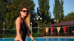 La blonde gracieuse utilise des lunettes de soleil sort de la grande piscine banque de vidéos