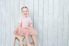 La blonde mignonne de petite fille s'assied sur une chaise sur un fond blanc images libres de droits