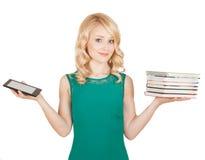 La blonde mince compare un comprimé et des livres Photos libres de droits