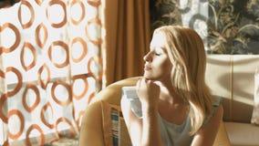 La blonde s'assied dans une chaise dans une chambre près de la fenêtre et apprécie le soleil banque de vidéos