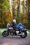 La blonde se trouve sur la grande moto Image stock