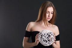 La blonde tient une sphère blanche Photo stock