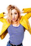 La blonde ?tonn?e de jeune fille dans une veste lumineuse jaune regarde la visionneuse images libres de droits