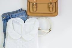 La blusa delle donne bianche del pizzo, blue jeans, una borsa marrone e una cintura bianca su un fondo bianco Le attrezzature cas fotografie stock libere da diritti