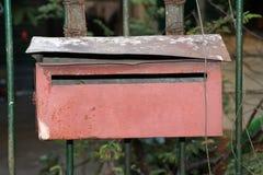 La boîte aux lettres rouge sur la barrière de fer photo libre de droits