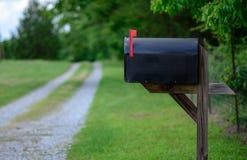 La boîte aux lettres rurale avec le drapeau a augmenté le long d'une route de gravier Images libres de droits