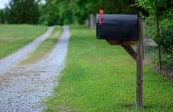 La boîte aux lettres rurale avec le drapeau a augmenté le long d'une route de gravier Photographie stock