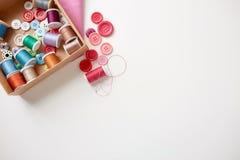 La boîte avec des bobines et la couture de fil se boutonne sur la table Photographie stock libre de droits