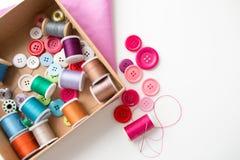 La boîte avec des bobines et la couture de fil se boutonne sur la table Photos stock
