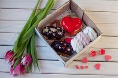 La boîte avec des eclairs, guimauve, gâteau s'est trouvée sur la table en bois près des tulipes Images stock