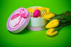 La boîte avec le fond de tulipes de macarons de couleur de ressort de baie pour des valentines enfantent le jour Pâques de femme  Photographie stock