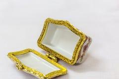 La boîte de bijou colorée minuscule avec de l'or platted le cuir embouti à un arrière-plan blanc Macro avec la profondeur du cham Photos stock