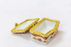 La boîte de bijou colorée minuscule avec de l'or platted le cuir embouti à un arrière-plan blanc Macro avec la profondeur du cham Photographie stock