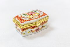 La boîte de bijou colorée minuscule avec de l'or platted le cuir embouti à un arrière-plan blanc Macro avec la profondeur du cham Photo stock