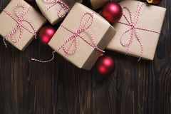 La boîte de cadeaux de Noël présente avec les boules rouges sur le fond en bois Image stock