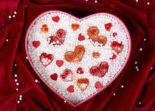 La boîte en forme de coeur a rempli de petites boules de mousse et de coeurs de papier fait main Photographie stock libre de droits