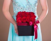 La boîte noire avec la rose de rouge fleurit dans des mains femelles Image stock