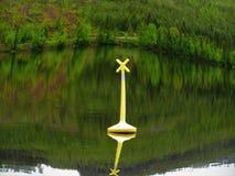La boa d'avvertimento gialla vi dice per guardare fuori per le onde contro terra fotografia stock