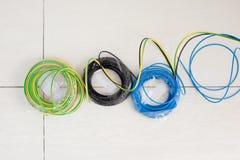 La bobina de cable eléctrico en tres colores ennegrece el azul y la tierra Foto de archivo