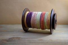 La bobina della ruota di filatura ha riempito di filato del handspun fatto della lana degli sheep's Fotografie Stock Libere da Diritti