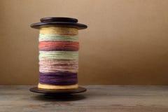 La bobina della ruota di filatura ha riempito di filato della mano fatto della lana degli sheep's contro un fondo della carta m Fotografia Stock Libera da Diritti