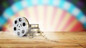 La bobina di film con un fondo 3d del cinema della striscia di pellicola rende sul blu Immagine Stock Libera da Diritti