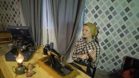 La bobina retra de la muchacha de la costurera rosca, disfruta del trabajo, cose con la máquina de coser de la vieja mano manual  almacen de video