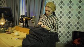 La bobina retra hermosa de la muchacha de la costurera rosca, cose con la máquina de coser de la vieja mano manual Mujer que trab almacen de video