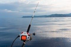La bobine électrique de pêche a monté sur une tige avec la mer dans le backgroun photo stock