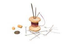 La bobine avec des fils, des aiguilles, le bouton et des perles d'isolement sur un fond blanc Images stock