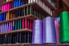 La bobine colorée de fil de couture a arrangé sur l'étagère en bois Photographie stock libre de droits