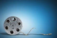 La bobine de film avec une bande 3d de film rendent sur le bleu Photographie stock
