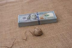 La bobine de la bobine de toile est placée sur des billets de banque de dollar US Photo libre de droits