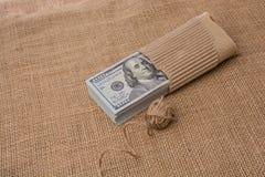 La bobine de la bobine de toile est placée sur des billets de banque de dollar US Images stock