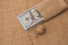 La bobine de la bobine de toile est placée sur des billets de banque de dollar US photos stock