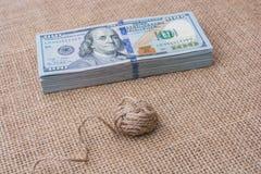 La bobine de la bobine de toile est placée sur des billets de banque de dollar US Photo stock