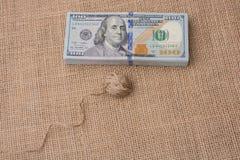 La bobine de la bobine de toile est placée sur des billets de banque de dollar US photographie stock