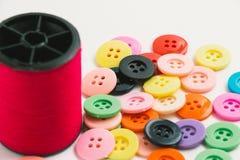 La bobine du fil et des boutons, cousent l'instrument sur le Ba blanc Images stock