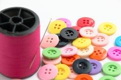 La bobine du fil et des boutons, cousent l'instrument sur le Ba blanc Photographie stock libre de droits