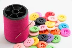 La bobine du fil et des boutons, cousent l'instrument sur le Ba blanc Photos stock