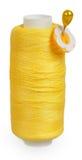 La bobine du fil jaune avec le bouton jaune sur la goupille Images libres de droits