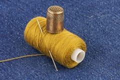 La bobine du jaune filète avec une aiguille en métal et un dé en métal Photographie stock libre de droits